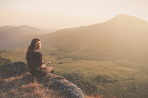 Hipster young girl with backpack enjoying sunset on peak of fogg